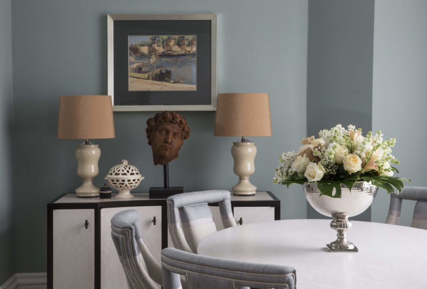The white table is surrounded by soft blue and white upholstered Parson chairs, while a dining room cabinet framed in black holds a pair of porcelain lamps flanking a copper colored statue head.