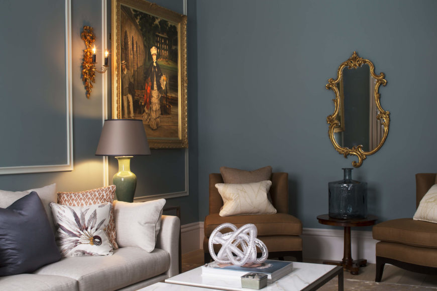 The room is packed with detail, including this freeform shaped mirror with gold leaf frame, armless accent chairs in brown, and a marble topped, black metal coffee table. Wall sconces and painting frames match the gold tones that pop against the soft blue walls.