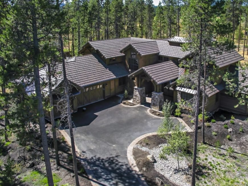 An aerial view of the home's driveway and front entrance, including the large covered entryway with stone supports and ornate woodwork. The enormous three-stall garage gives this home a L-shape. The landscaping is sparse and easy to care for, and the home is surrounded by tall pines.
