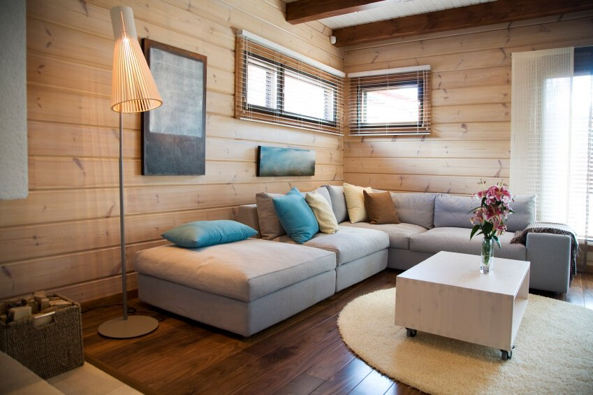 """A chic and minimalist living room with light wood paneling and a wheeled coffee table with a single glass vase. The light gray couch has turquoise, pale yellow, and brown throw pillows. The mixture of the wood panelling and the minimalist makes this space a """"modern contemporary cabin."""""""