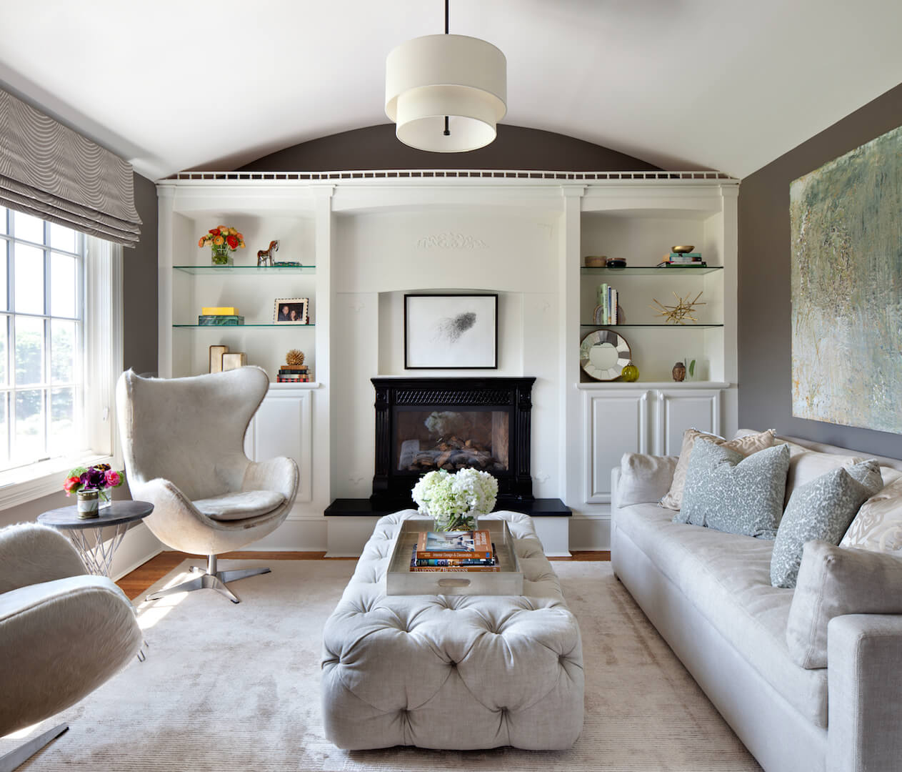 The sitting room adjacent to the primary suite has several cozy and furry chairs, a beige sofa, and a beautiful button-tufted upholstered ottoman. A metallic tray on top allows the ottoman to double as a coffee table. On the far wall is an enclosed fireplace and built-in shelving.