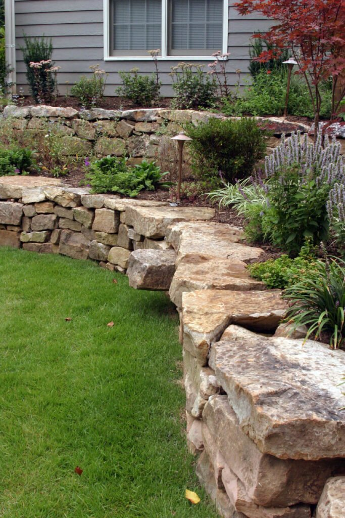 A hand-laid retaining wall made out of natural stone. Two terraces are filled with low maintenance landscaping. The terraces smooth out angle between the much higher house and the lawn.