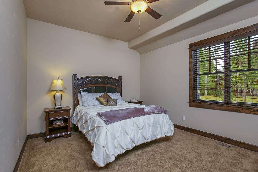 Another of the bedrooms on the main level, with light brown carpet and multi-tonal wood trim. The simple furniture of this bedroom consists of a rich dark wood bed frame and nightstand with contrasting white bedding. The room is lit by the double windows, a ceiling fan light, and the elegant table lamp next to the bed.