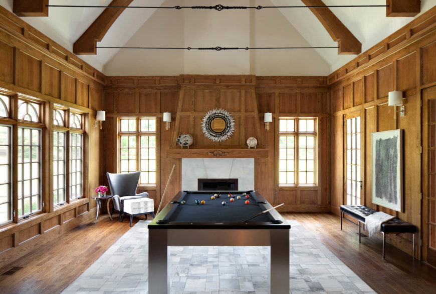 The main spot for guests in this home is the den, which is host to a large billiards table and a series of beautiful, large windows. The center of the floor is a large area rug in geometrics, surrounded by hardwood. On the far wall between two windows is a massive wooden fireplace with a white tile mantle.