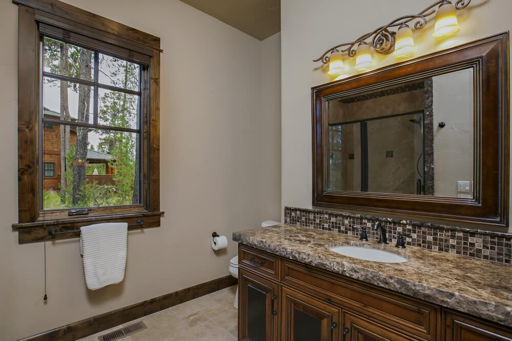Adjacent to the laundry room and mudroom is a main floor bathroom with matching cabinets to the other two and a towel rack attached to the bottom trim of the window, which looks out on the neighboring house. The light fixtures are slightly different in this bathroom, with a long series of lights above the mirror instead of on the sides.
