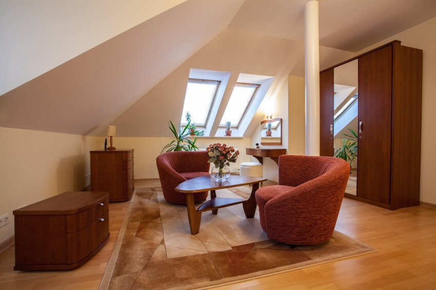 This attic has been converted into a small apartment-like living space, with a seating area, vanity, and bedroom.