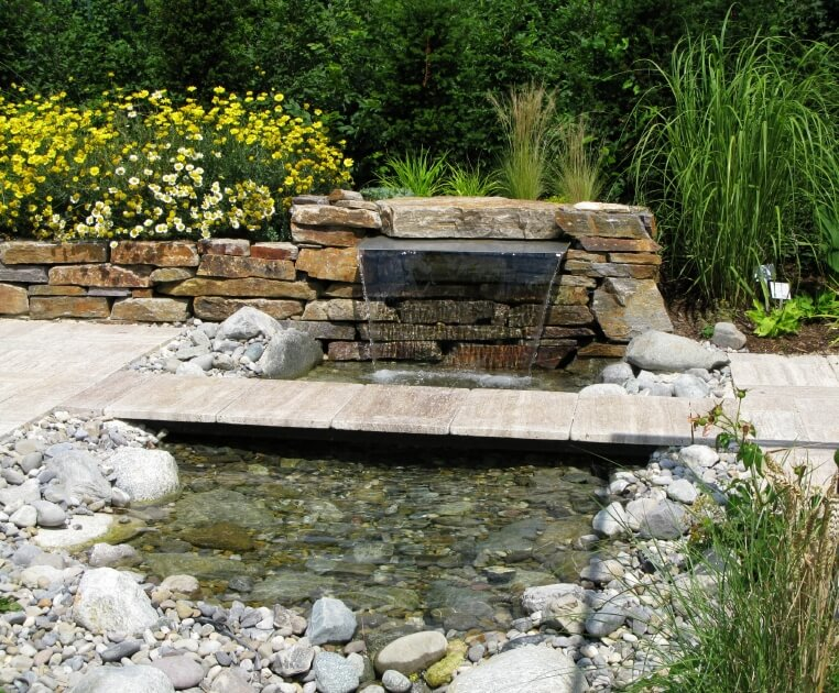 A shallow pond fed by a cascading fountain tucked into the stone edging. A narrow stone footbridge connects the two sides of the pathway.
