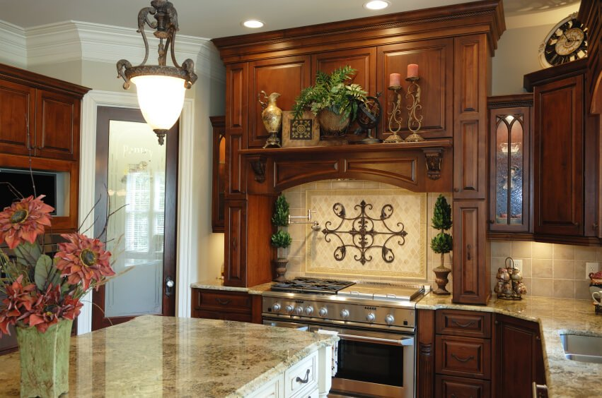 An old-world style dark wood kitchen with light marble countertops and a beige stone backsplash. The center arrangement above the stove has a decorative iron design in the middle.