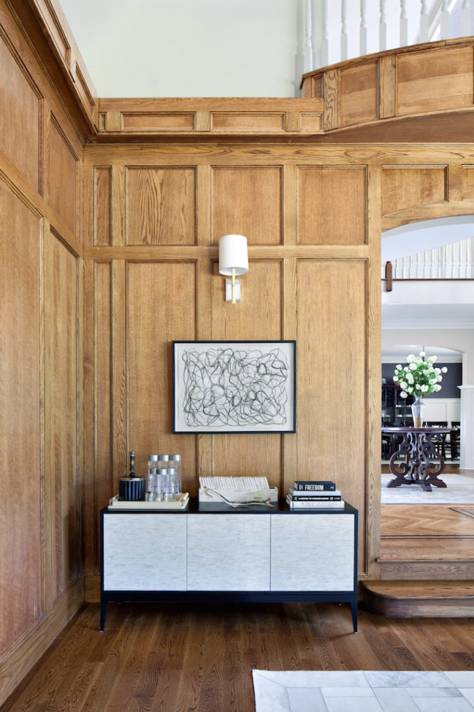 The den entrance is off of the foyer, and immediately to the right of the entrance is a small buffet area with a stunning piece of contemporary art. Visible through the archway is the ornate dark wood table with a vase of white flowers that brightens the foyer.