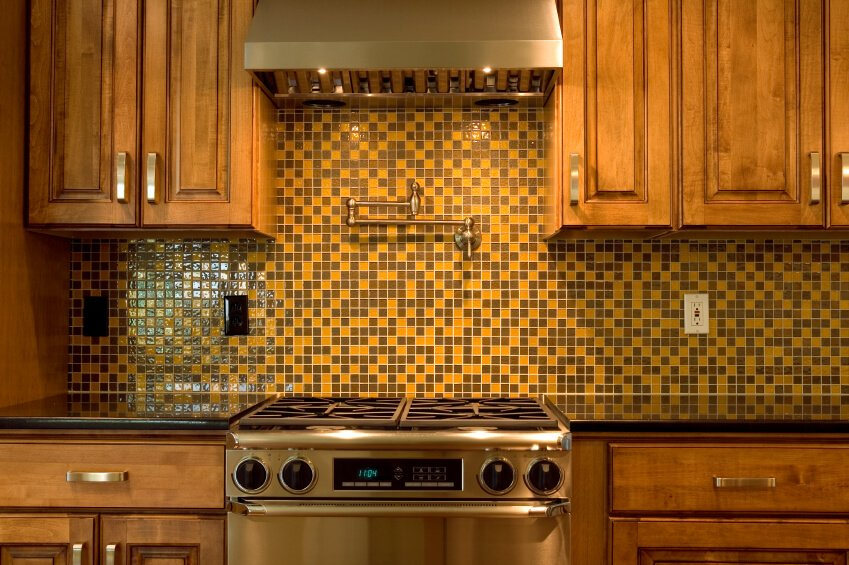 A retro backsplash in mustard and chocolate brown glass 1 inch mosaic tiles.