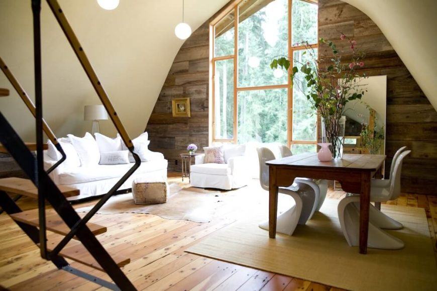 In the upper levels of the barn is the separate apartment. The lower part has a living area that closely matches the living room on the main level, and an adjacent dining table with modern white chairs.
