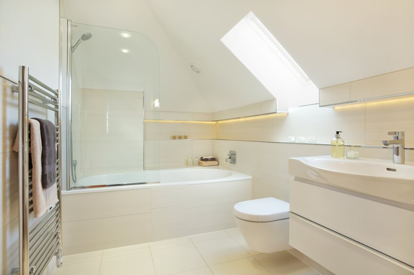 A typical small bathroom in white with a combination shower and bathtub. The line of shelving along the walls has under-cabinet lighting broken only by the skylight.