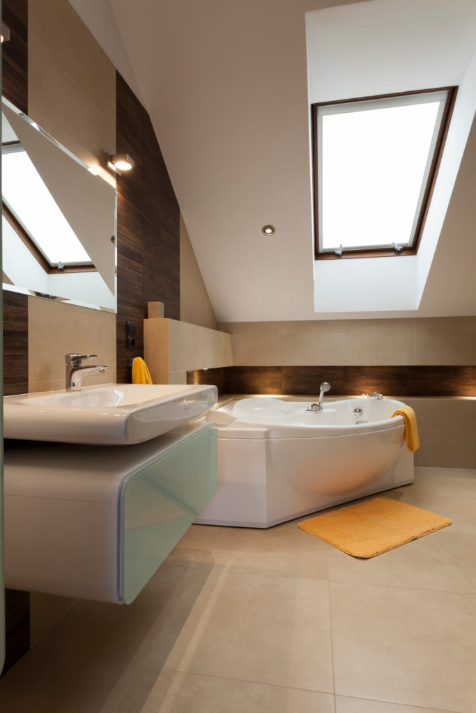 A modern bathroom in beige tile. A sleek, shallow vessel sink rests above a modern vanity with a frosted glass panel on the front. The soaking tub bows out at the middle for extra room. Yellow accents add a pop of color.