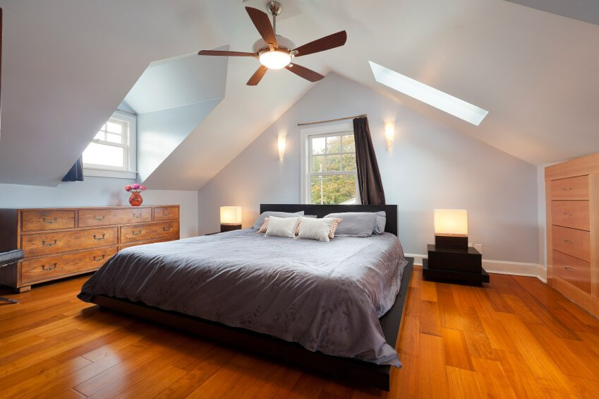 Sconces and cube lights along with multiple skylights and windows create a warm and welcoming attic bedroom. The dark drapery and bed linens contrast well with the light wall color and honey-colored hardwood floors.