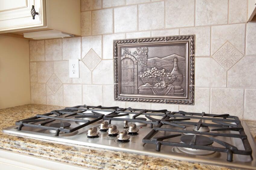 A ceramic tile backsplash with a metal medallion above the range in a pastoral scene.