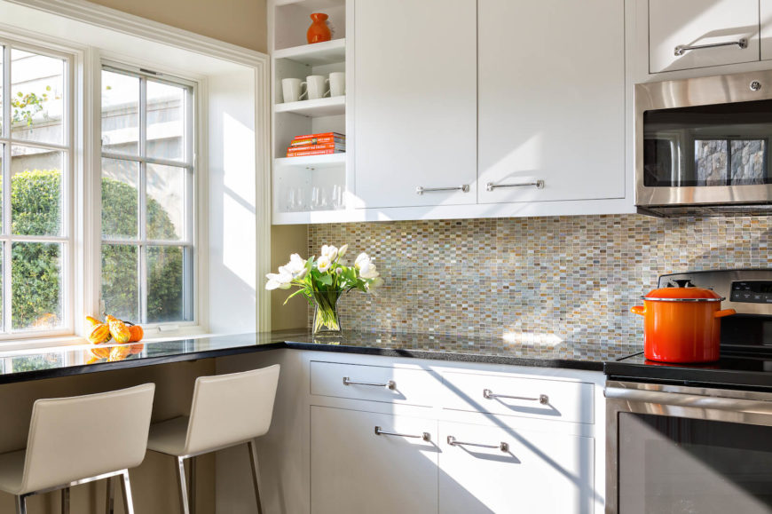 A close up of the eat-in bar facing the window and the beautiful multi-tonal glass backsplash that reaches all the way to the bottom of the wall cabinets. Open shelving on the left is a perfect place to display accents.