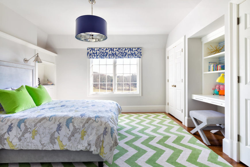 A child's bedroom in white and green, featuring a fun dinosaur bedspread. The area rug is a chevon pattern in a light, springy green. The secondary accent color is a bold deep blue, in the light fixture and on the window coverings.