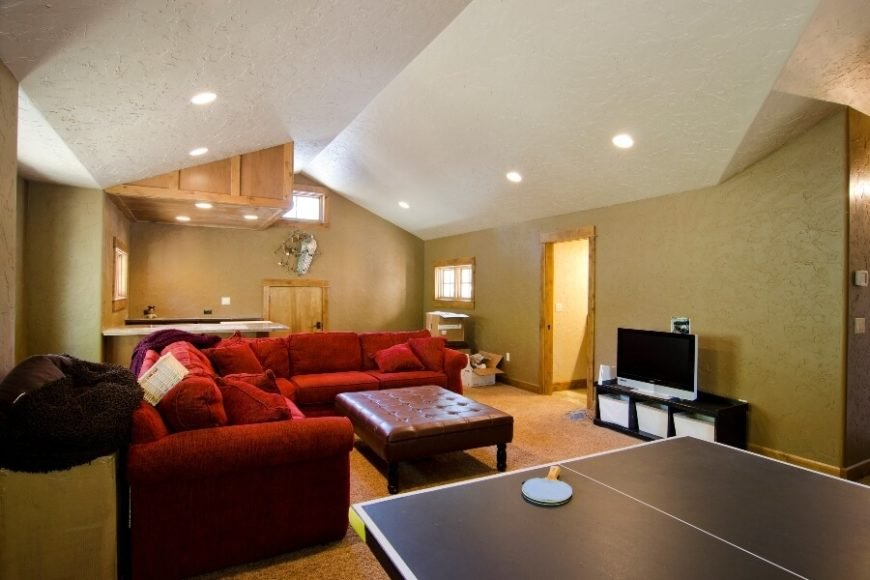 """The bonus room on the second floor has been turned into a family room/game room, complete with an entertainment center and a half-bath off the right wall. The small crawl space door on the far wall leads to additional """"attic"""" storage space."""
