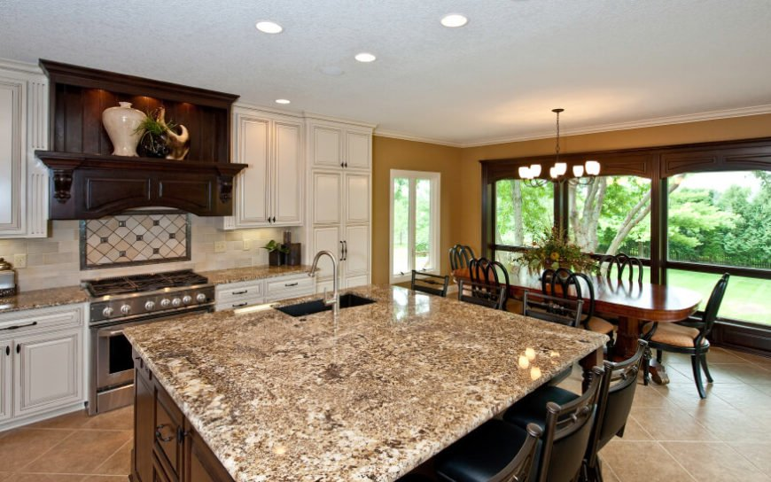 An elegant kitchen with an adjacent dining room. The busy brown and cream granite countertops are contrasted by the light, subtle backsplash.