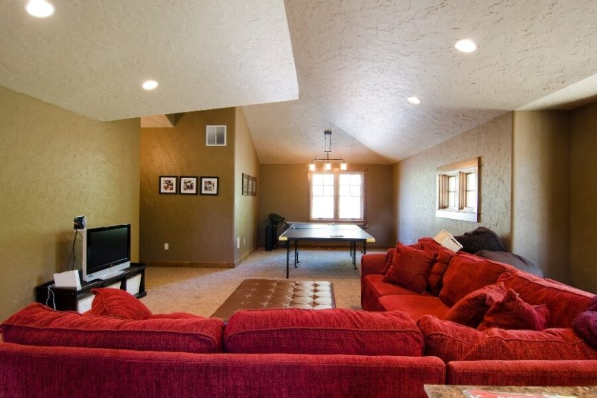 A view of the family room's bright red velour sectional from the opposite side of the room, showing the spacious game space that is occupied by a ping-pong table. The faux-leather ottoman is light enough to be easily moved out of the way if needed when playing Wii.