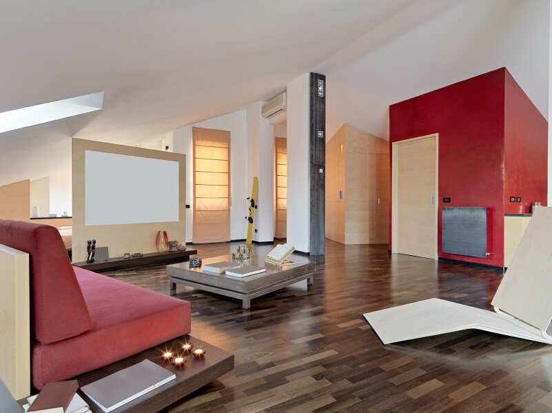 A converted attic with several spaces. Behind the screen is the bedroom area, while the majority of the attic is a living room with multi-toned wood floors and bold red accents.