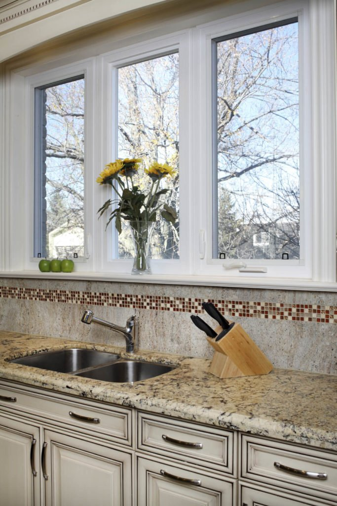 A solid, seamless stone backsplash with a strip of cream, gray, and red glass mosaic tiles around the perimeter.