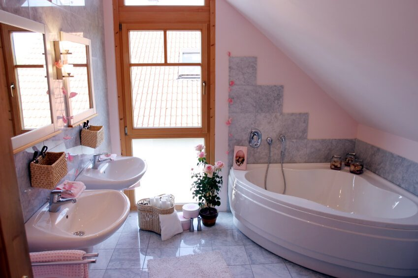 A very feminine bathroom in light gray tile and pink. The pale pink walls are matched with roses and pink towels. Each wall-mounted sink has its own mirror.