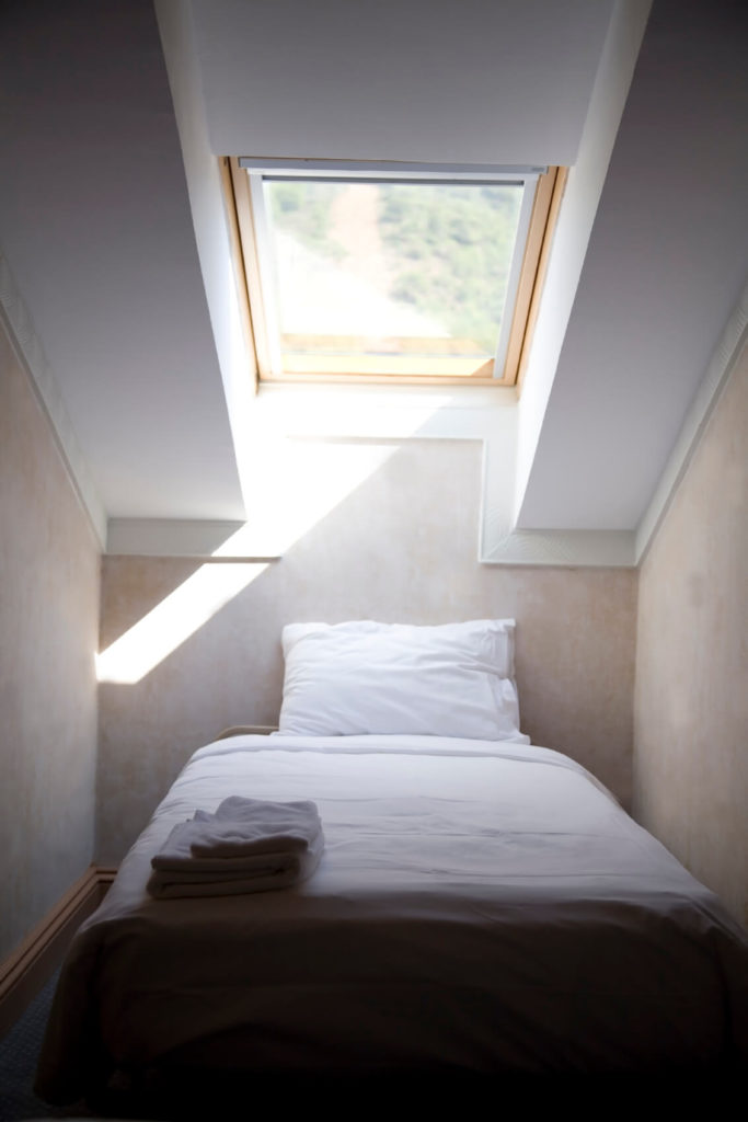 A sleeping area tucked neatly into this attic nook with a large skylight illuminating the space.