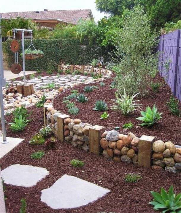 A simple terrace created with wooden blocks, chicken wire, and large stones for a rustic look. The landscaping is simple and low maintenance.