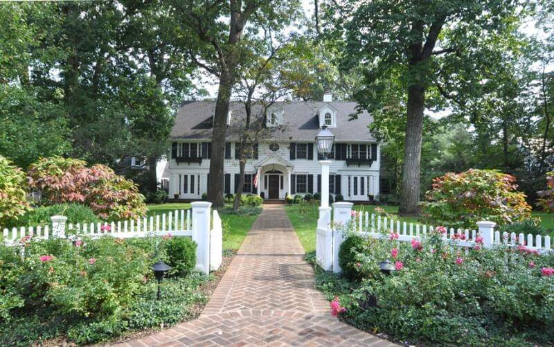 A charming white picket fence around the perimeter of a stately colonial home. The gate swings open along a long brick walkway to the front door.