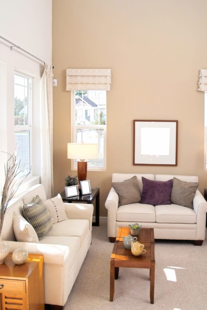 A living room in light taupe and ivory with side tables in varying shades of wood from a dark finish to a more natural oak. The cathedral ceilings help give this small space an open, large feel.