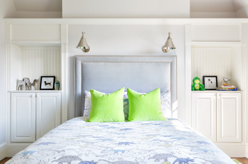 A final look at the adorable dinosaur bedding brightened up by lime green throw pillows. The built-in shelves on either side of the upholstered head board eliminate the need for nightstands.