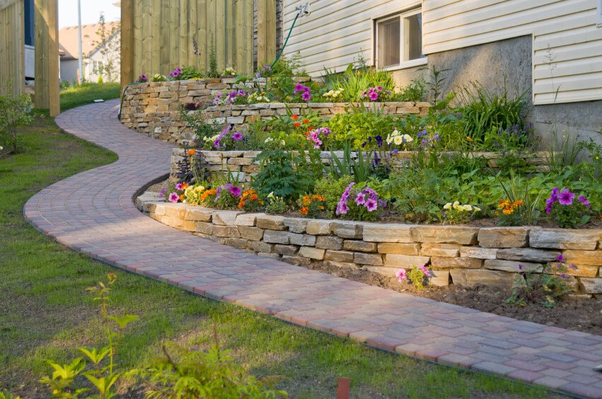 A residential terrace garden along a winding stone path along the side of the home.