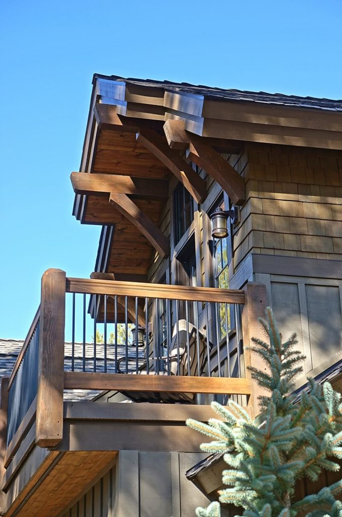A view of the balcony that overlooks the backyard from the exterior, better showing the size of the balcony and the wood and iron railings.