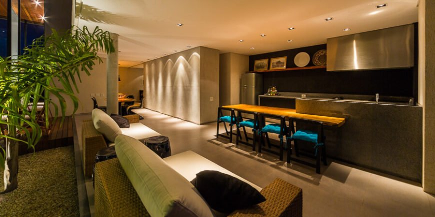 The interior in this space is opened entirely to the pool and patio area, with a wicker sectional marking the divide.