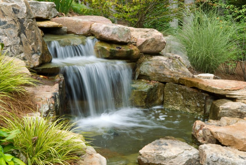 This water feature focuses on the large waterfall tumbling into a small, shallow pool at the bottom. The entire structure is encased by large stones and surrounded by grasses.