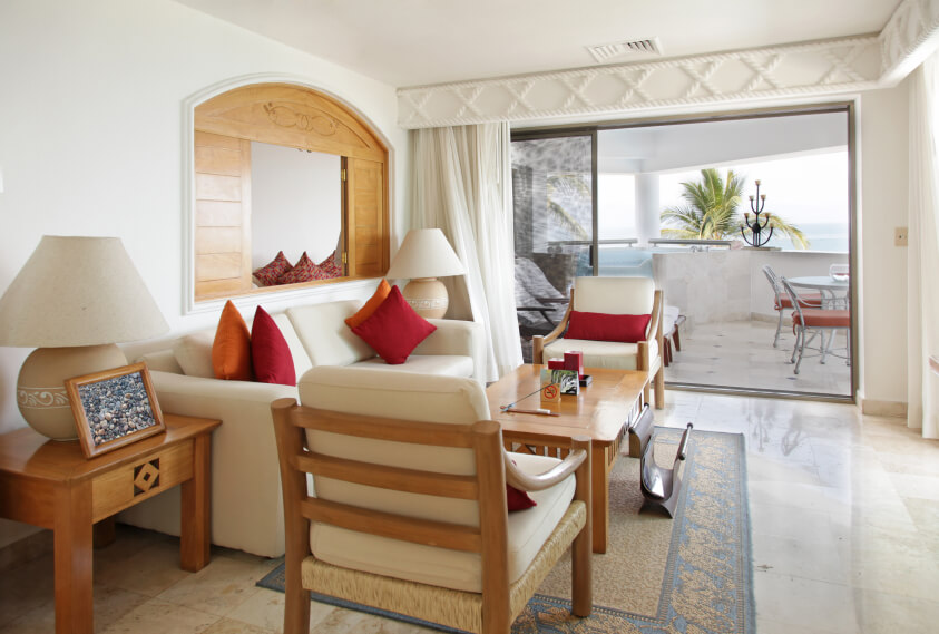 A small living room that leads out onto the covered patio. A wooden passthrough above the sofa peers into an adjacent room. The pocket door includes a screen that can be closed so that the owners can enjoy the breeze, but don't need to deal with bugs.