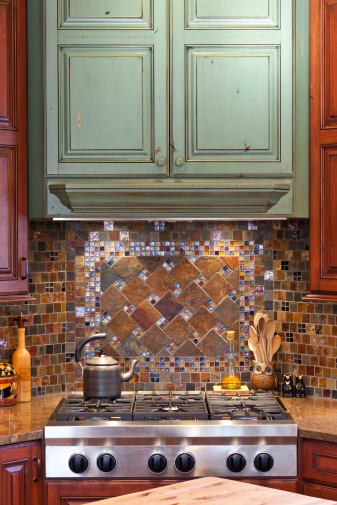 A glass-tile backsplash with multiple colored tiles and accents of beautiful, glittering glass mosaic tiles.