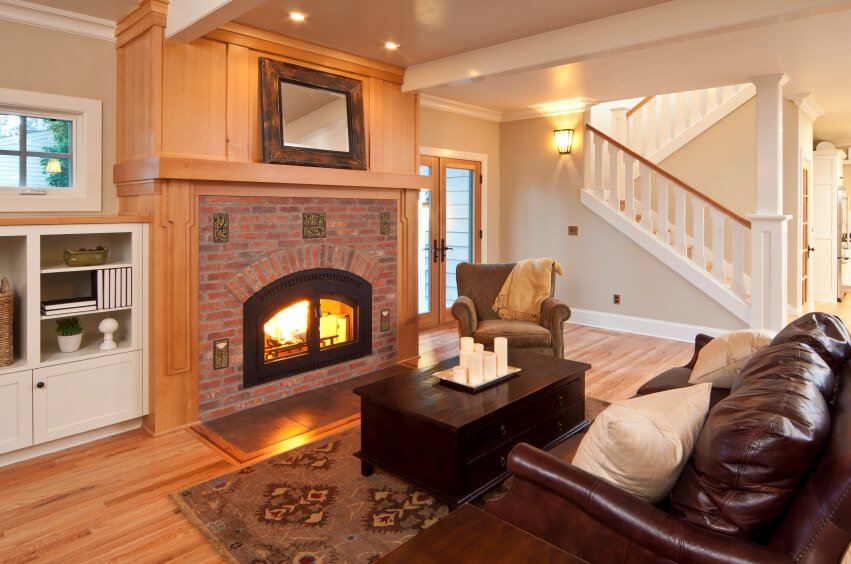 A living room off of the foyer with a large wooden and brick mantle around the enclosed fireplace. Doors can be opened up to enjoy a more open flame. The small space has a leather loveseat, coffee table, and a cozy armchair. French doors lead out to the backyard. The warm brick of the fireplace gives this room a more rustic atmosphere.