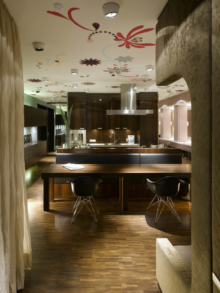 Turning around, we see the living room as part of the large central space comprising the kitchen and dining areas of the home. Rich hardwood shelving and flooring spread everywhere.