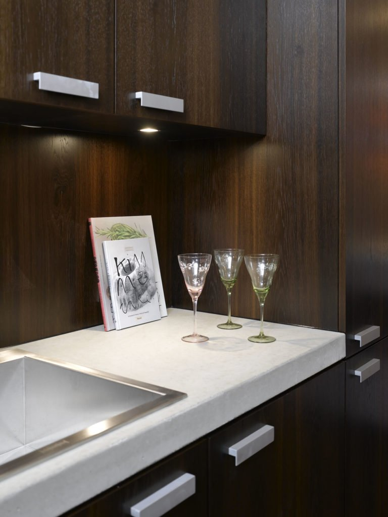 Minimalist hardware mounts and an angular, deep sink share the sleek utilitarian look.