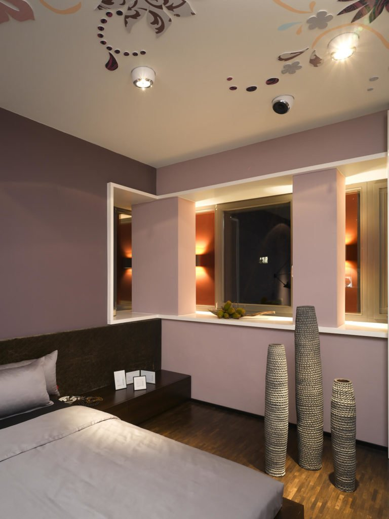 A wall-length low wooden shelf flanks the bed, while the sculptures stand next to the low divide overlooking the hall.