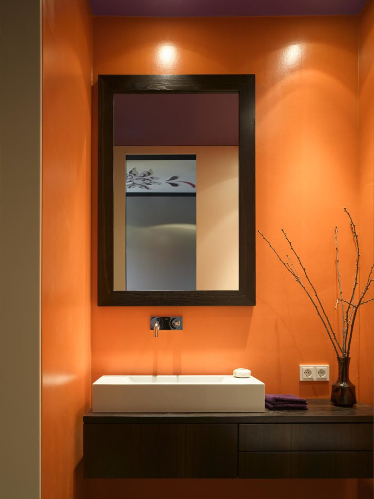 Primary bath pops in bright orange and purple tones. Here is the floating dark wood vanity holding a large rectangular vessel sink.
