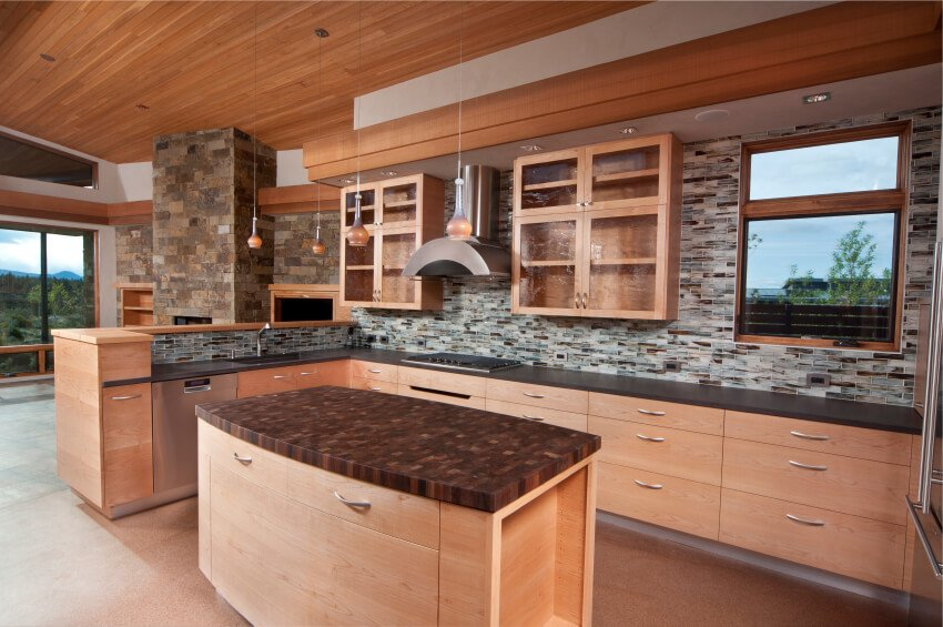 A contemporary light wood kitchen with a backsplash that extends all the way to the overhanging section above the wall cabinets that has recessed lighting.