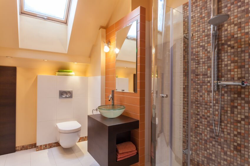 A contemporary attic bathroom in pale peach, orange, and red. The mix of colors in the mosaic tile help tie this color palette together.