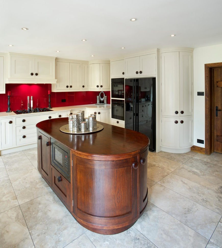 A white kitchen with rounded cabinets and an oval kitchen island in a rich dark hardwood. The stunning deep red of the backsplash immediately draws the eye.