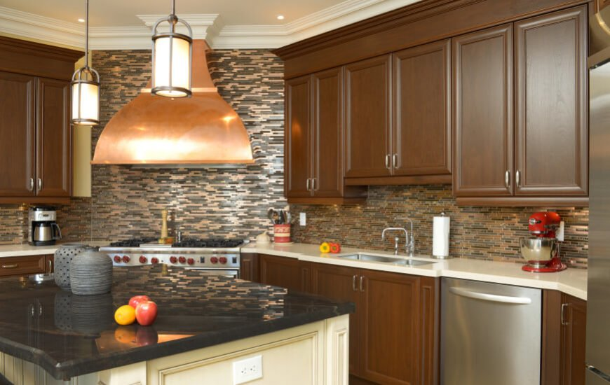 A kitchen with an interesting glass tile backsplash that looks different depending on the angle of the light. Copper elements add shine to the design