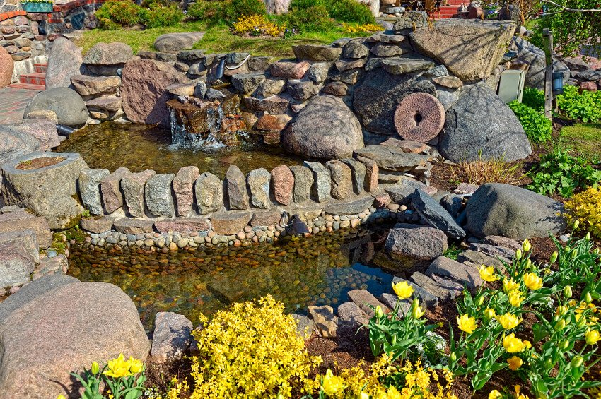 A unique pond with two tiers. The top tier has a small rock waterfall. Fields of tulips and other plants surround the rock enclosure.