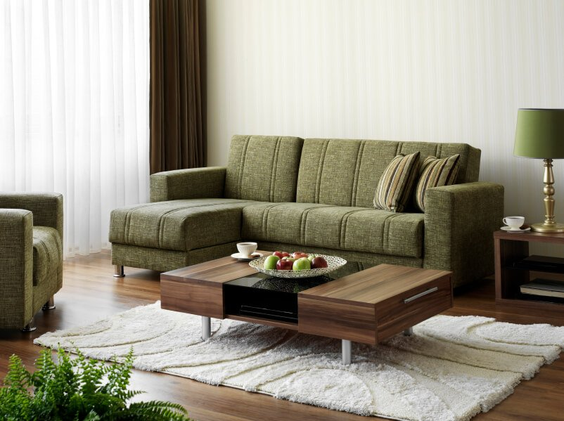 A contemporary living room with olive green furniture and a shaggy white area rug with a concentric pattern. The natural wood coffee table has a block of synthetic black in the center, which adds a modern twist to this design. The curtains consist of sheer whites behind thicker chocolate brown drapes. A wicker fruit bowl and houseplants act as accents.