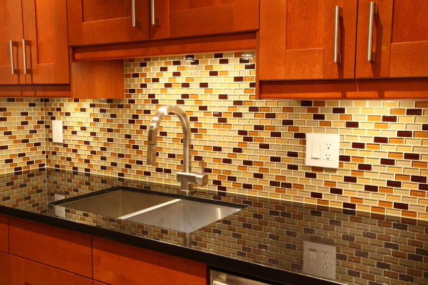 A glass-tile backsplash with accents of gold and red.